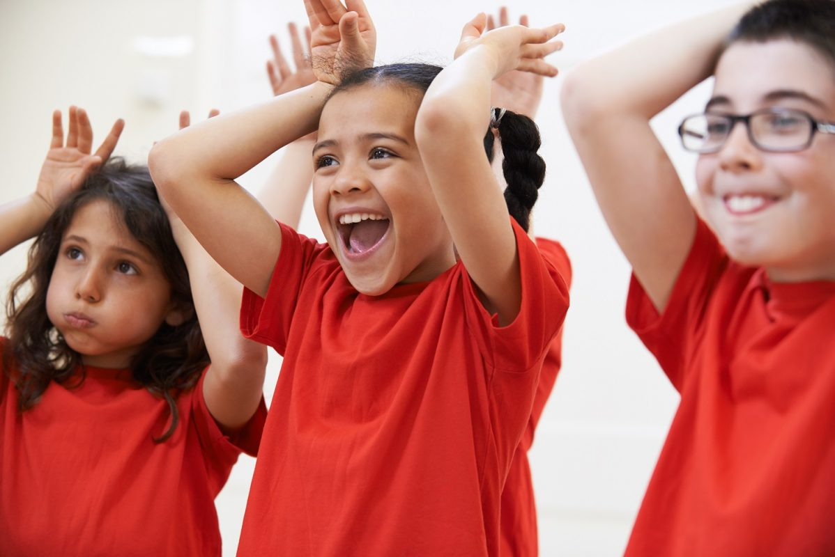 three children taking part in a music class putting their hands up like bunny ears