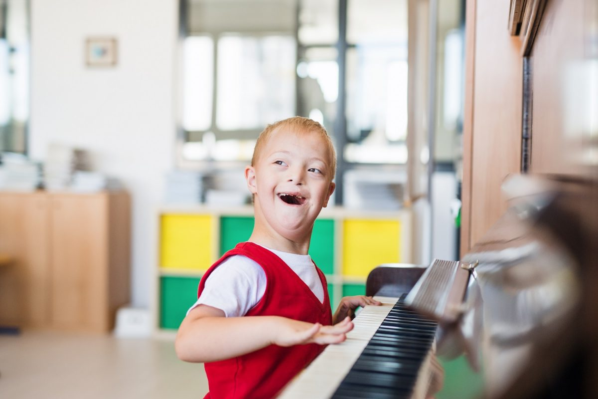 Little boy playing piano and smiling