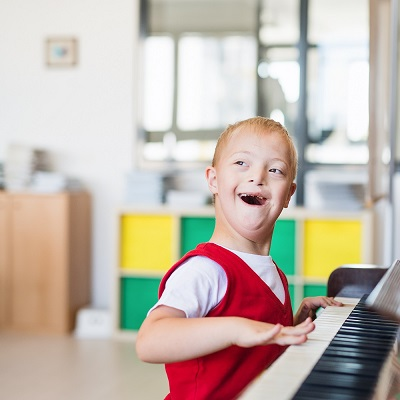 Young boy playing the piano and smiling