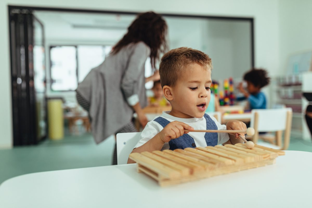 Little boy playing a xylophone in class