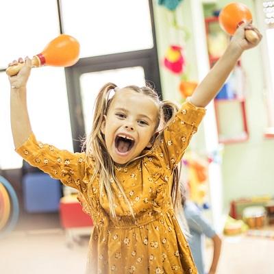 Little girl smiling and shaking maracas