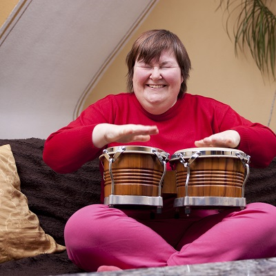Woman playing the bongos and smiling