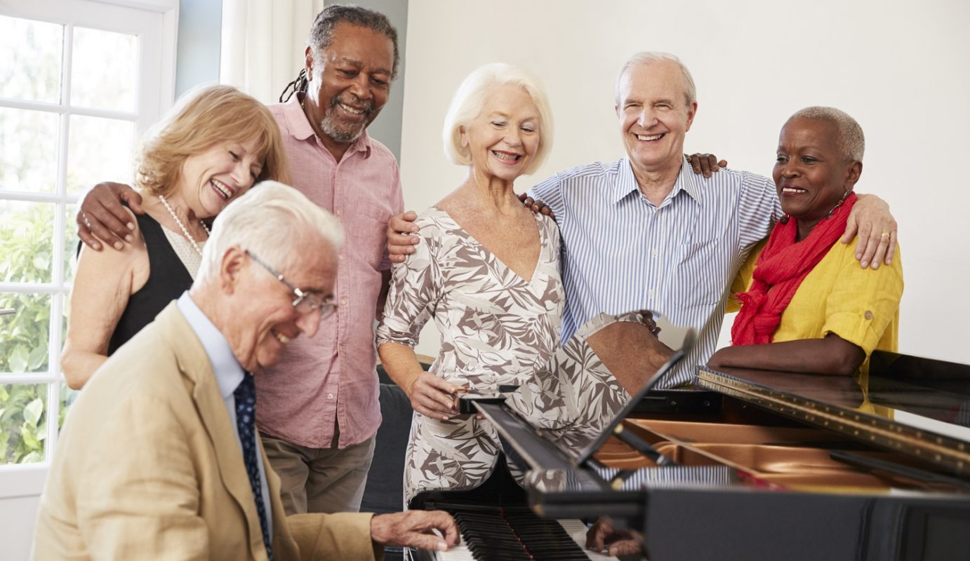 Group of adults smiling around a man playing piano