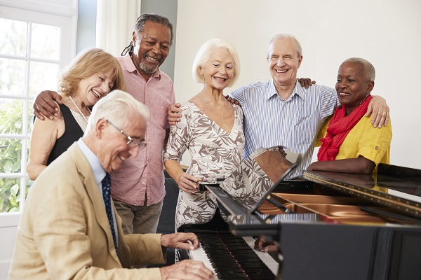 Picture of adults stood around a piano and smiling